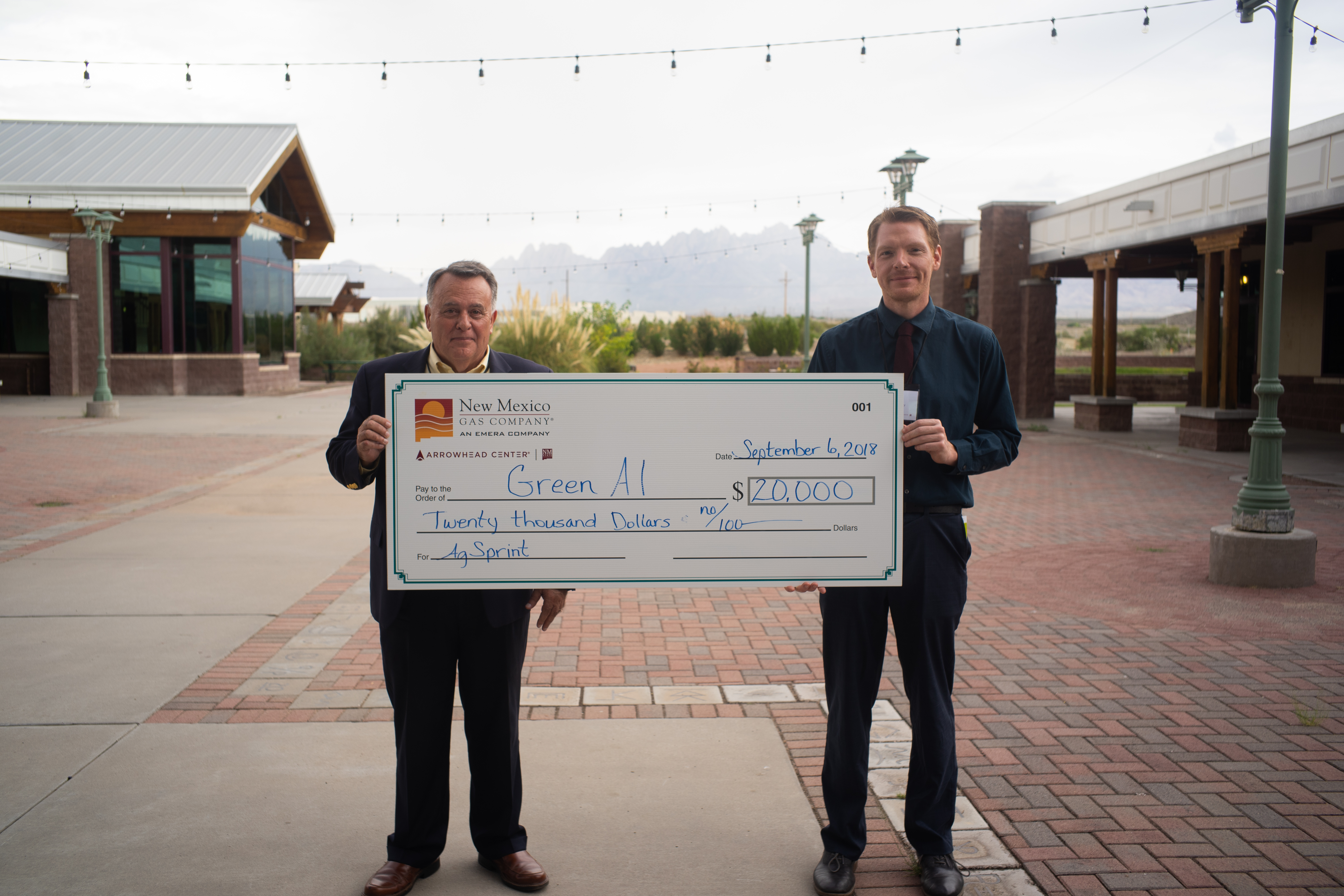 Cliff Hudson (left), chief technology officer of Systems Technology Solutions, recently secured a $20,000 investment for GreenAI, an innovative sensor technology for <br> crop analytics, through the AgSprint business accelerator program at New Mexico State University 's Arrowhead Center. The check was presented to Hudson at the <br>second annual AgAssembly conference in Las Cruces. At right is Del Mackey, program specialist at Arrowhead Center. (NMSU courtesy photo)